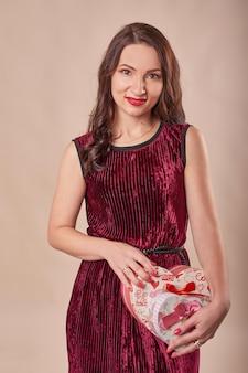 Ritratto della donna allegra in contenitori di regalo rossi della tenuta del vestito