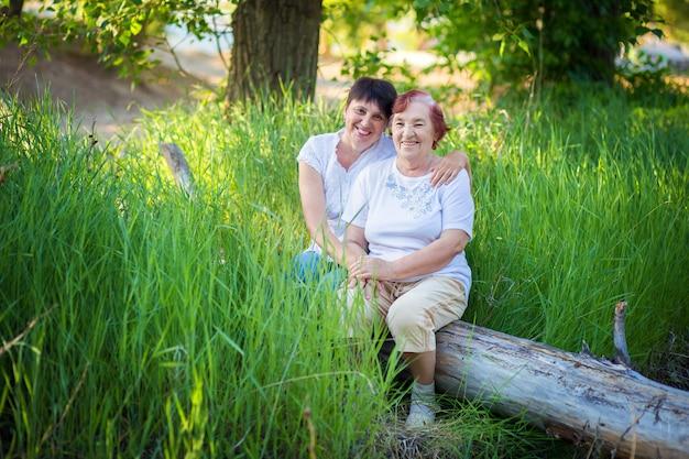 Ritratto della donna anziana con la figlia adulta all'aperto