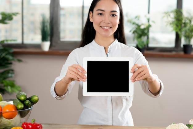 Ritratto della donna asiatica che mostra compressa digitale dello schermo in bianco in cucina