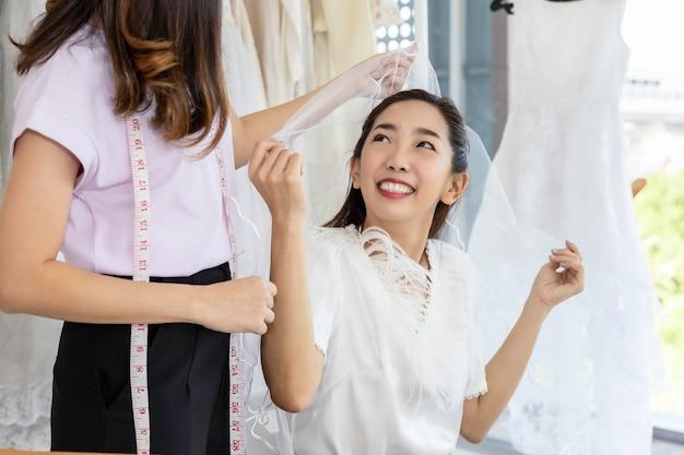 Ritratto della donna asiatica che sceglie vestito in un negozio con l'assistente del sarto.