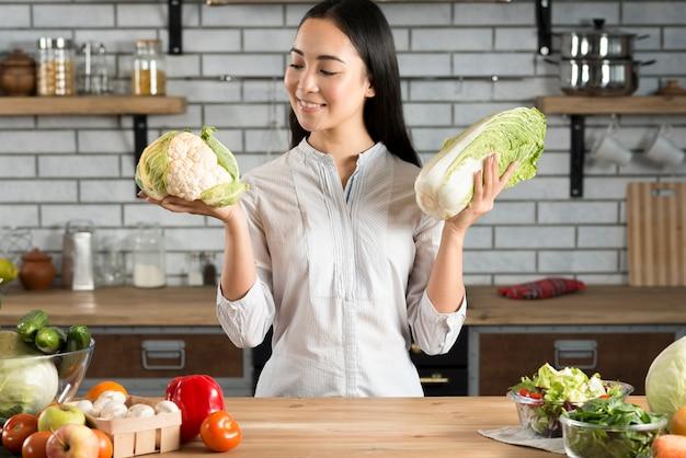 Ritratto della donna asiatica che tiene cavolfiore e lattuga verdi in cucina