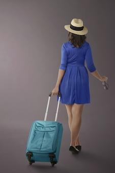 Ritratto della donna asiatica che viaggia con la valigia