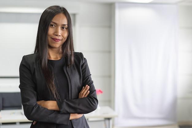 Ritratto della donna asiatica sicura di affari che si leva in piedi nell'ufficio.