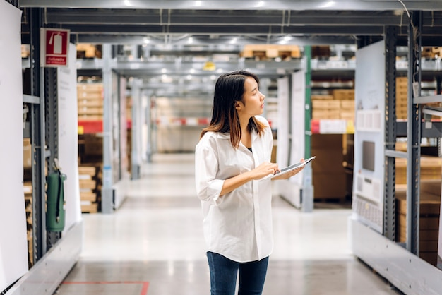 Ritratto della donna asiatica sorridente dell'operaio manager in piedi e dettagli dell'ordine sul computer tablet per il controllo di merci e forniture sugli scaffali con sfondo di merci in magazzino