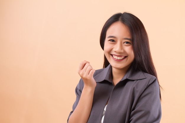 Ritratto della donna asiatica sorridente felice di affari che posa la sua mano che tiene qualcosa