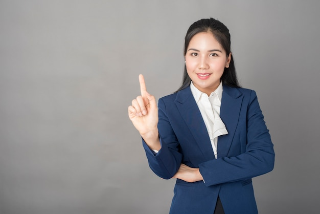Ritratto della donna astuta di affari in vestito blu che indica con la sua barretta