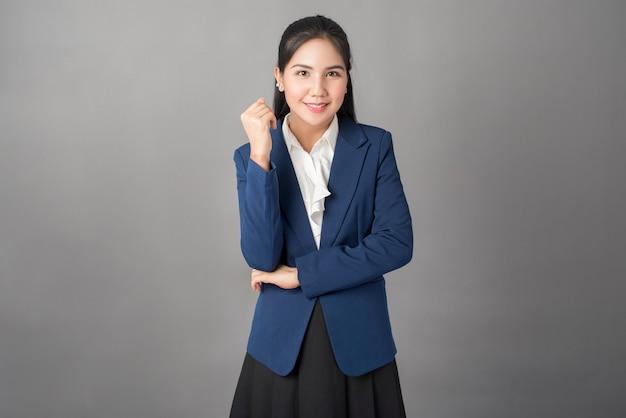 Ritratto della donna astuta di affari in vestito blu su fondo grigio, colpo dello studio