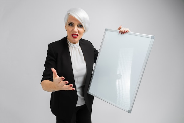 Ritratto della donna bionda che tiene un bordo magnetico in sue mani isolate su fondo