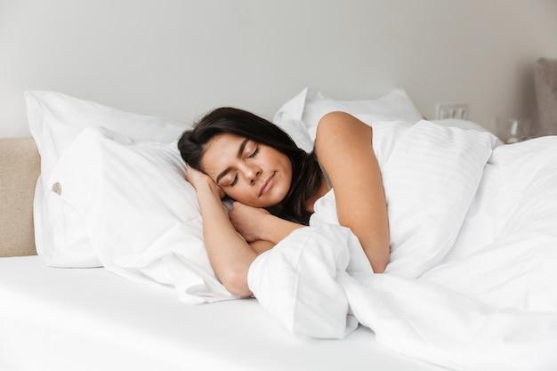 Ritratto della donna castana che dorme a casa a letto sul cuscino, con lettiera bianca