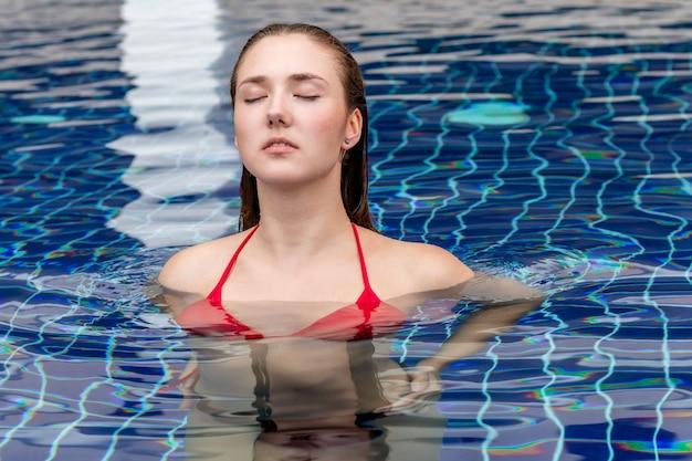 Ritratto della donna caucasica di modo che sta nella piscina.