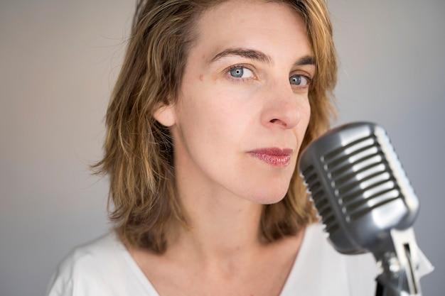 Ritratto della donna caucasica seria che canta una canzone con un microfono d'argento d'annata. donna che tiene un microfono vintage e l'esecuzione di musica dal vivo.