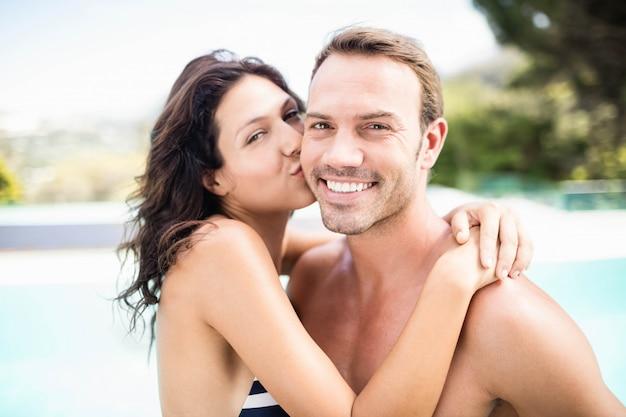 Ritratto della donna che bacia uomo vicino allo stagno un giorno soleggiato