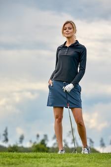 Ritratto della donna che gioca a golf su un campo verde