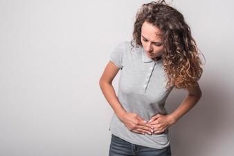 Ritratto della donna che ha mal di stomaco contro fondo grigio