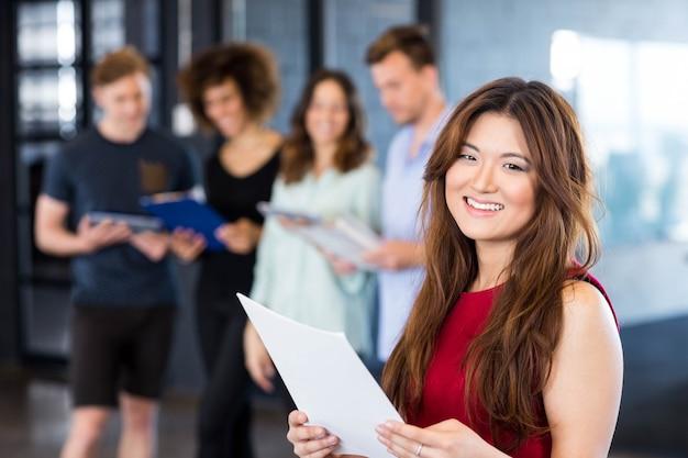 Ritratto della donna che legge un documento mentre colleghi che stanno dietro nell'ufficio