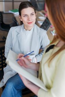 Ritratto della donna che si siede sulla tazza di caffè della tenuta della sedia che esamina il suo collega