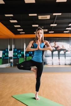 Ritratto della donna che sta nell'yoga che posa alla palestra