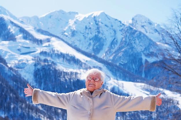 Ritratto della donna dai capelli grigi senior in vetri che sorride in natura. la donna anziana felice sveglia prima vede le montagne nell'inverno un giorno soleggiato. il modo di vivere degli anziani il concetto di pensione.