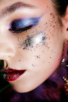 Ritratto della donna del primo piano con trucco e le scintille fumosi degli occhi.
