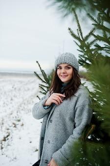 Ritratto della donna delicata in cappotto e cappello grigi contro l'albero di natale all'aperto.