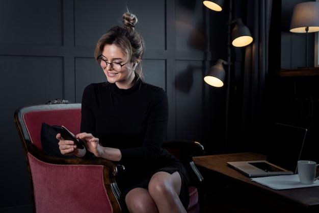 Ritratto della donna di affari adulta con gli occhiali all'ufficio