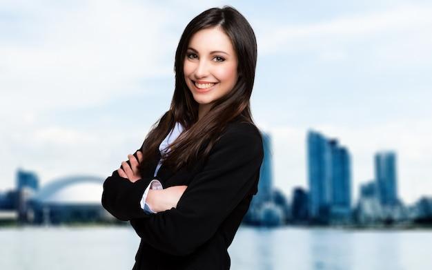 Ritratto della donna di affari all'aperto contro un orizzonte moderno della città in