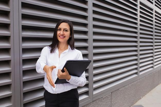 Ritratto della donna di affari allegra che allunga mano per la stretta di mano