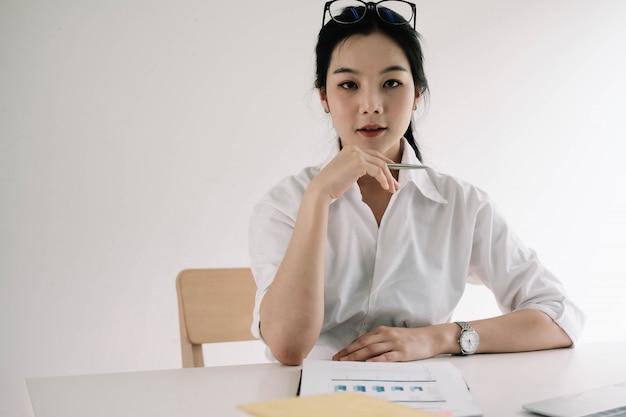 Ritratto della donna di affari asiatica attraente che lavora al computer portatile per il piano di vendita