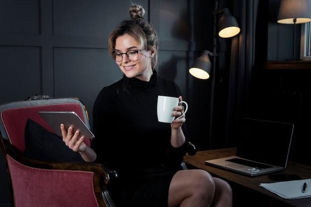 Ritratto della donna di affari astuta che tiene una tazza