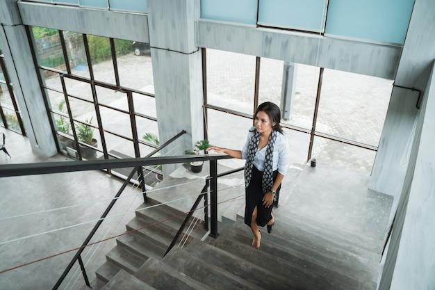 Ritratto della donna di affari che cammina sulle scale da solo