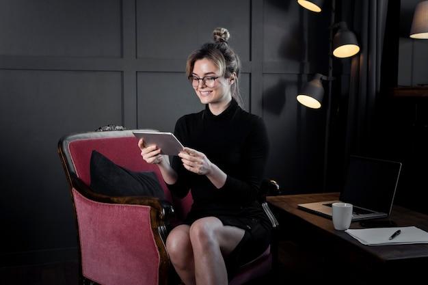 Ritratto della donna di affari che controlla una compressa