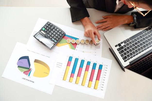 Ritratto della donna di affari che impila significato delle monete di aumento di profitto o investimento o risparmio di denaro