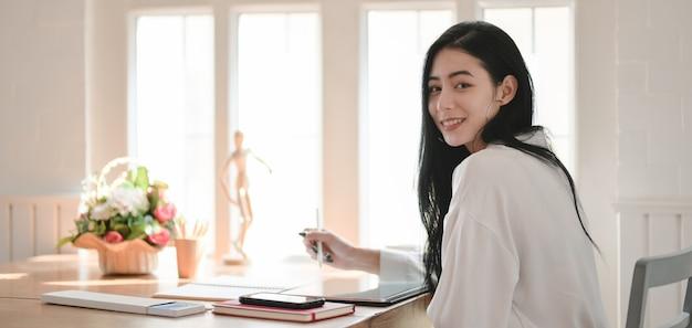 Ritratto della donna di affari che lavora al suo progetto e che sorride alla macchina fotografica nella stanza comoda