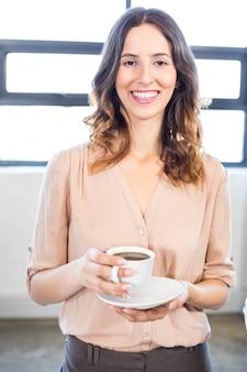 Ritratto della donna di affari che mangia una tazza di tè in ufficio