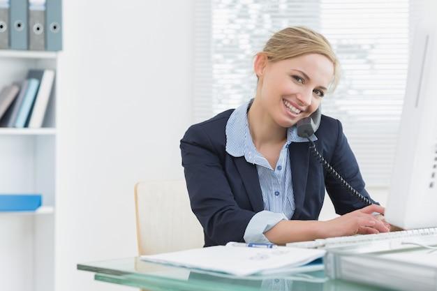 Ritratto della donna di affari che per mezzo del telefono e del computer allo scrittorio
