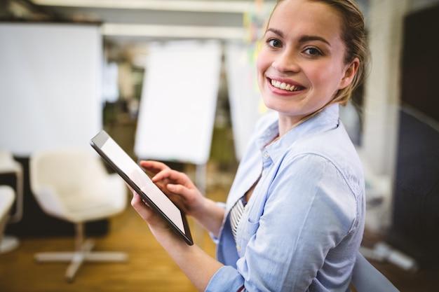 Ritratto della donna di affari che per mezzo della compressa digitale