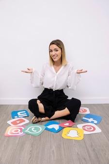 Ritratto della donna di affari che si siede con gesturing sociale delle icone di media