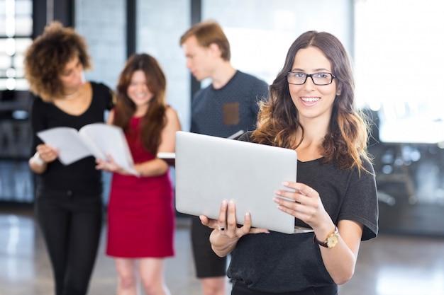 Ritratto della donna di affari che usando discussione dei colleghi e del computer portatile
