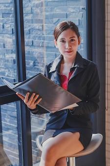 Ritratto della donna di affari con il rapporto finanziario in ufficio