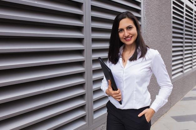 Ritratto della donna di affari felice che cammina con la cartella all'aperto