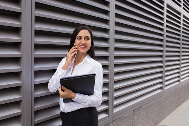 Ritratto della donna di affari felice che parla sul telefono cellulare all'aperto