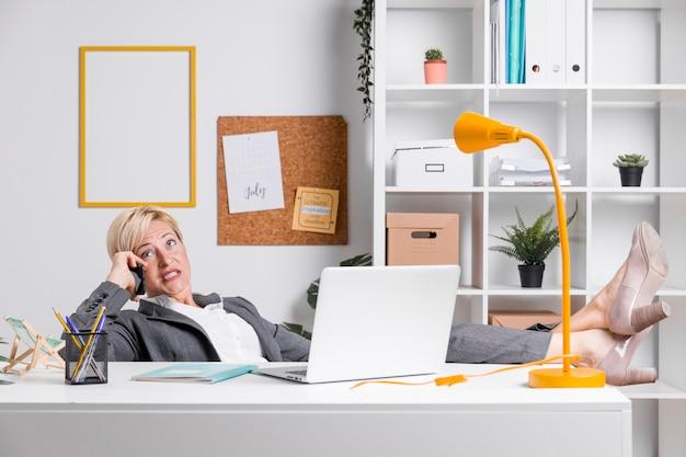 Ritratto della donna di affari invecchiata centrale in ufficio