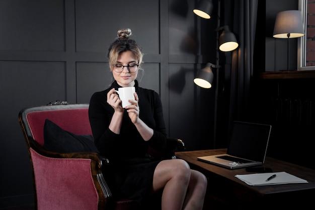 Ritratto della donna di affari sicura che mangia caffè