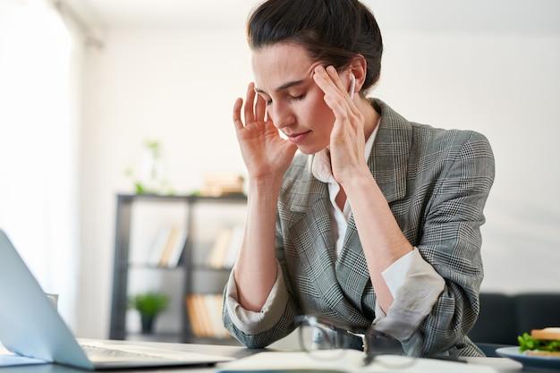 Ritratto della donna di affari sollecitata che soffre dall'emicrania mentre lavorando nell'ufficio, spazio della copia