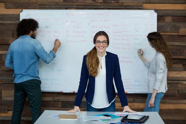 Ritratto della donna di affari sorridente che si appoggia sulla tabella mentre lavoro del collega