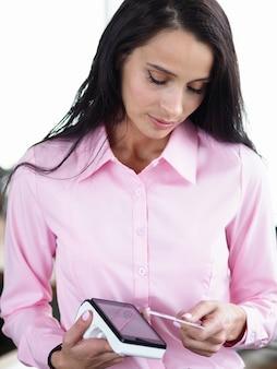 Ritratto della donna di affari sveglia che paga i servizi tramite servizio terminale. bella businesslady con punto di accesso e carta. concetto bancario e di pagamento