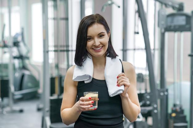 Ritratto della donna di forma fisica con bicchiere d'acqua con il limone