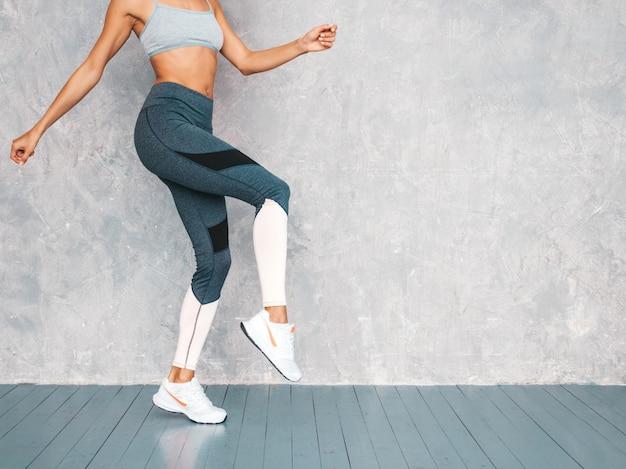 Ritratto della donna di forma fisica in abbigliamento sportivo che sembra sicuro. giovane femmina che indossa abiti sportivi bello modello con il corpo abbronzato perfetto salto femminile nello studio vicino alla parete grigia