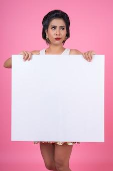 Ritratto della donna di modo che visualizza insegna bianca