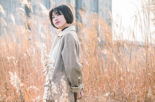 Ritratto della donna di stile che si leva in piedi in mezzo del campo a lamella
